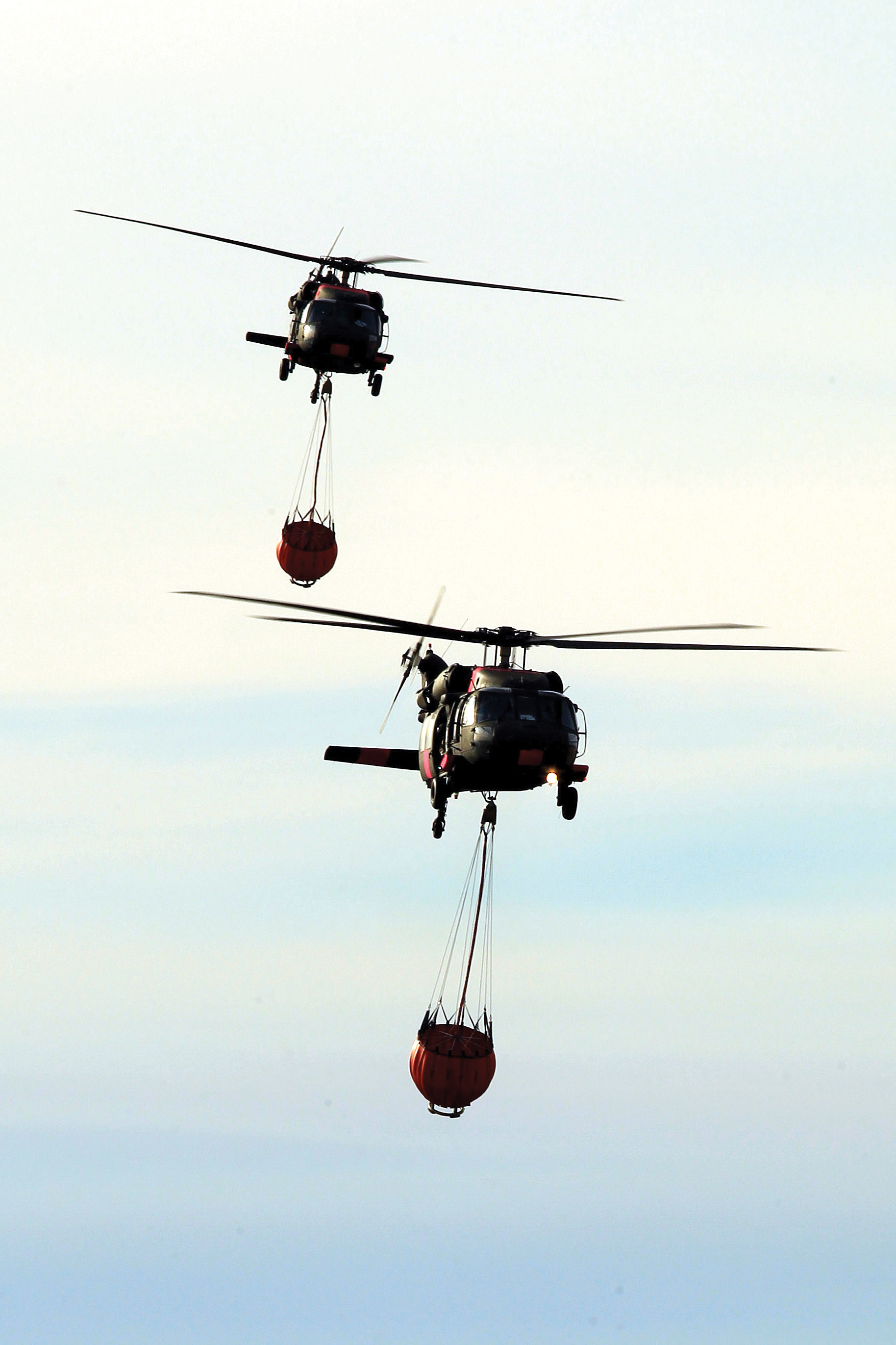 A pair of California National Guard UH-60 Black Hawk helicopters from B Company, 1st Battalion, 140th Aviation Regiment, return to Camarillo Airport in Camarillo, California, Sun., Dec. 10, 2017, after making water drops on the Thomas Fire burning in Ventura County. (U.S. Air National Guard photo by Senior Airman Crystal Housman)