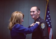 Chief Michael Morris is presented with his chief's badge by his wife, Nicki Morris. After serving as CI's Acting Police Chief for the past several months, Chief Morris was sworn-in as Chief on Friday, March 16. Photo credit to the CI Police Instagram page.