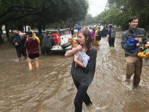 A woman holds her dog as she walks through the flood following Hurricane Harvey.
