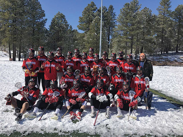 CI's Lacrosse Club poses for a team photo in the snow. Photo credit to the Lacrosse Club