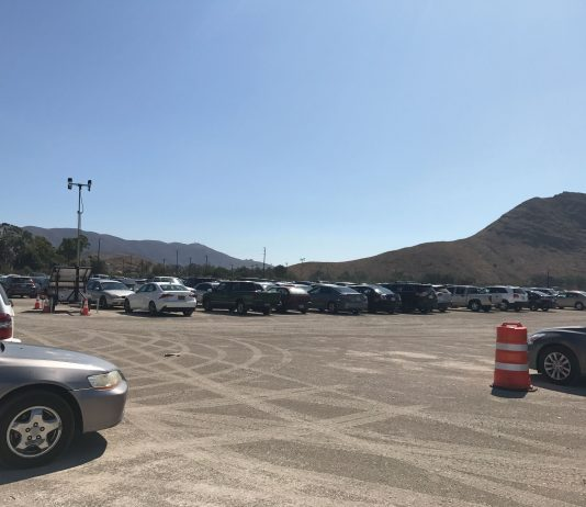 Cars parked in the dirt lot on campus.
