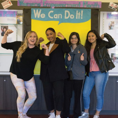 "Students pose in front of a ""We Can Do It!"" poster in the Student Union. The poster, along with photos of women throughout history, were set up in the Student Union to celebrate Women's History Month. Photo credit to Dennys Rico."