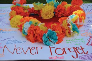 "Students signed a poster with a heart cutout filled with paper flowers at the ""Remember the 17"" walkout. The sign includes statements such as ""Never Forget"" and ""May your beautiful souls rest in paradise"" meant to honor the 17 lives lost in the Stoneman Douglas High School shooting. Photo credit to Jazzminn Morecraft"