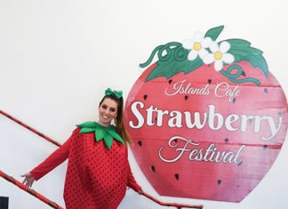 Lorena Gonzalez poses in front of a strawberry sign during the Strawberry Festival. Islands Café celebrated the 7th Annual Strawberry Festival on April 17. Photo credit to Debbie Anaya.