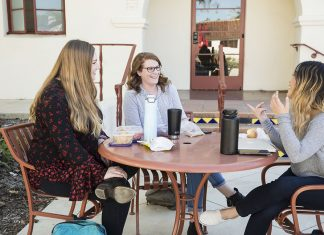 Three students sit around a table and enjoy a meal while they converse with one another. Photo credit to CI Communication and Marketing.