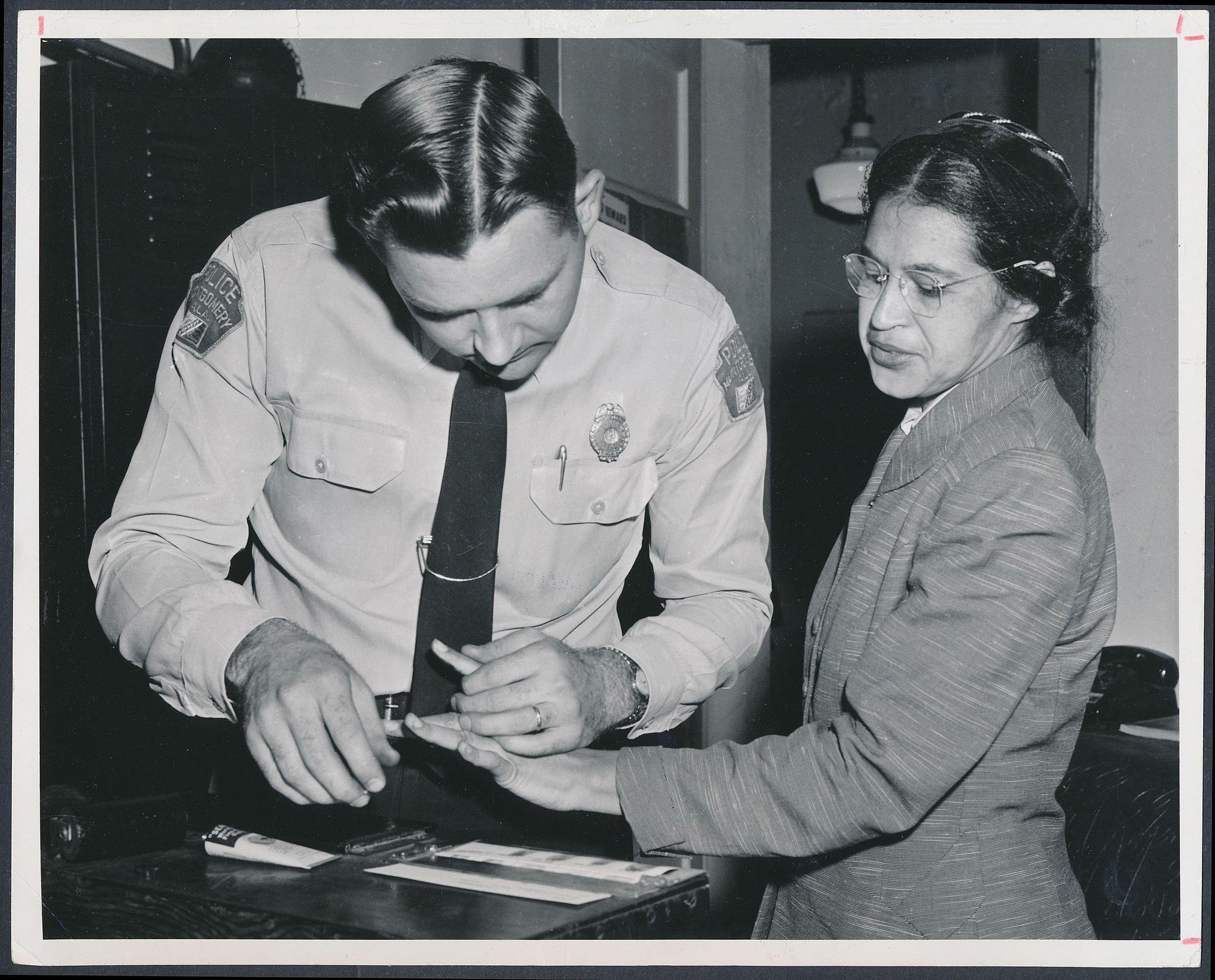 Rosa Parks being Fingerprinted in a police station.