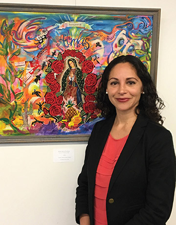 Professor Georgina Guzman poses in front of artwork at an event. On March 9, Professor Guzman was recognized by the California Association of Teachers of English and won an award for college classroom excellence. Photo credit to CSUCI.