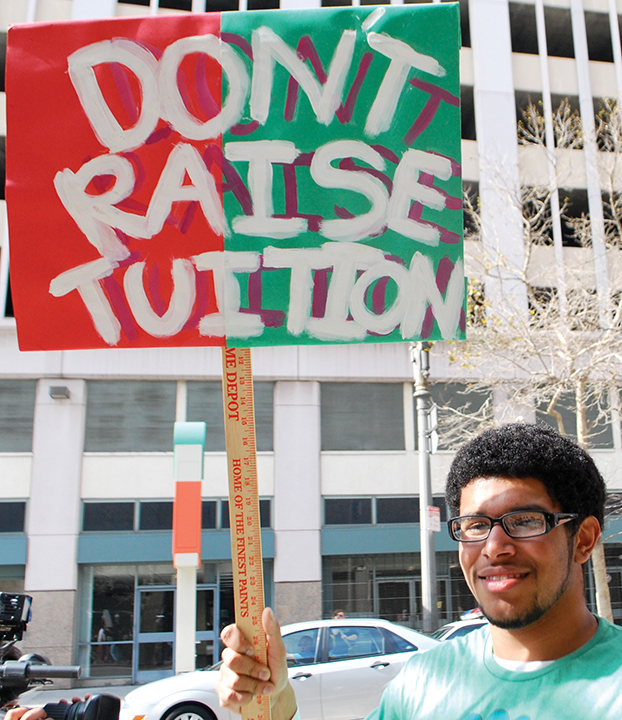 """A protestor holding a sign that says """"Don't Raise Tuition."""" Photo credit to Neon Tommy."""